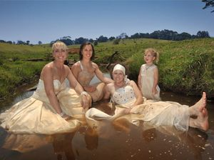 Brides get down and dirty for wedding dress trashing record