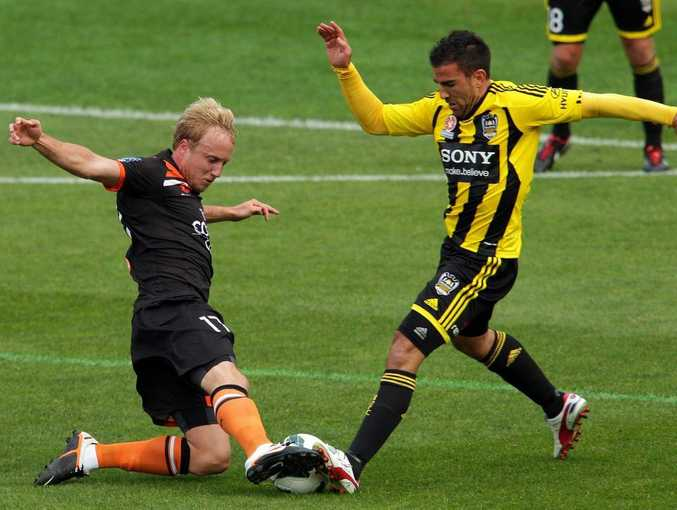 Mitch Nichols of the Roar and Manny Muscat of the Phoenix compete for the ball during the round three A-League match between the Wellington Phoenix and Brisbane Roar at Westpac Stadium on October 21, 2012 in Wellington, New Zealand.