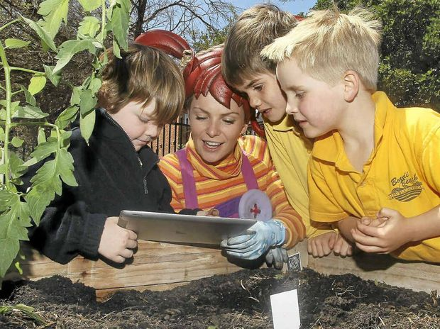 "GETTING DOWN: Dirtgirl helps school children plant their own ""smart seeds"" using the dirtgirlworld app on an iPad at Bondi Beach Public School."