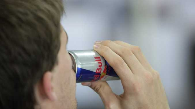 Drinking a Red Bull Energy Drink.