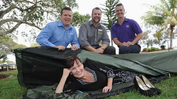 Fraser Coast Regional Council chief executive officer Lisa Desmond tries out one of the swags that local bosses will camp out in with Darren Bosley of the Fraser Coast Chronicle, Troy Sorrensen of the Hervey Bay RSL and Adam Healey of Forty Winks.