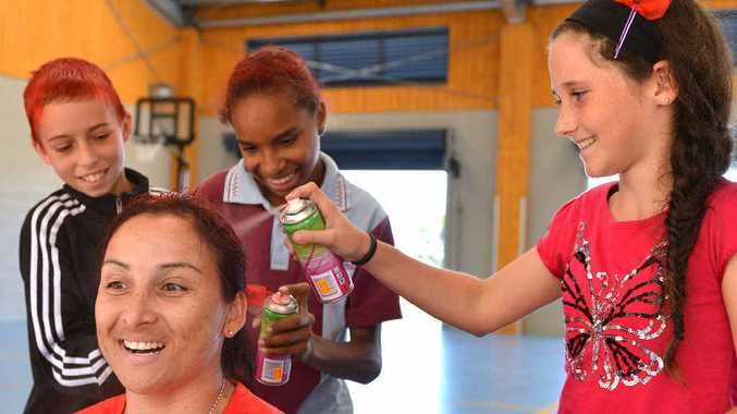 SAFETY MESSAGE: Slade Point State School students Rory Conroy, Leysha Emery-Gesah and Teagan Coates spray paint Detective Senior Sergeant Sam Bliss's hair red to mark Day For Daniel.