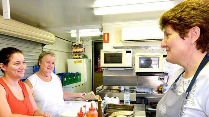 Victoria Park State School canteen volunteers Anita Clough and June Howard help tuckshop convenor Sue Behan print lunch orders from an online ordering system.