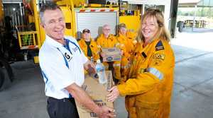 Brothers Leagues Club Bar manager Mark Halls hands over one of the cartons of water donated to the Rural Fire Brigade. Ripley member Tracey Olivieri accepts the water. Photo: Rob Williams / The Queensland Times