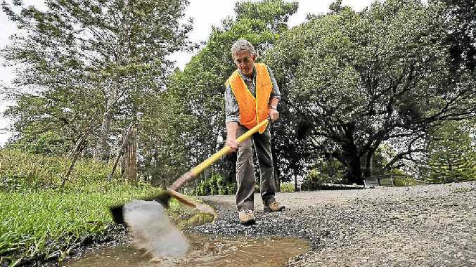 DIGGING IN: Councillor David Yarnall shovelling water from a 10cm deep pothole on Keerong Rd at The Channon. He has suggested giving residents the equipment to fix roads themselves to speed up the rate of repairs. Doug Eaton