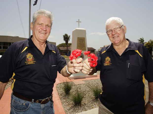 Caboolture RSL sub-branch members Glenn Willmann and Bruce Miller hold up poppies in remembrance.