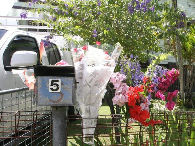 Floral tributes placed near the letterbox of 5 Bracher St where an elderly couple died on Tuesday.
