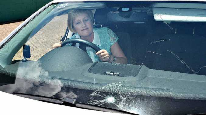 Cecily Bazeley surveys the damage done by a golf ball hitting her windscreen while she was driving.
