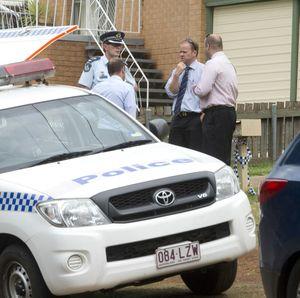 Police investigators keep vigil over the Hogg St crime scene.