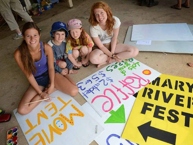 FESTIVE YOUNGSTERS: Lena Pfuetzenreuter, from Germany, and Luke and Moya Dennis and Jessica Kellner, also from Germany paint signs for today's Mary River Festival.