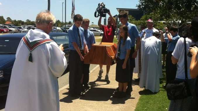 A holy relic of St Francis Xavier, his hand and forearm, will arrive in Ballina tonight. Here it is pictured being escorted by school students during a stop at Hervey Bay.