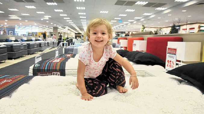 Two-year-old Marlee McKenna from Pacific Paradise tests out the bedding section at Domayne.