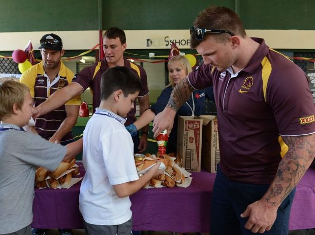 Churchill State School students Kale Harris and Josh Etherden having her lunch served up by Broncos players, Scott Anderson, Nick Slyney and Josh McGuire, after the school tuckshop won a competition run by Hans.