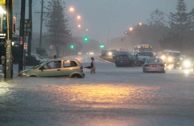 FLASHBACK: Torrential rain floods Alexandra Pde at Alexandra Headland – and one vehicle was swamped and washed down the street – in March.