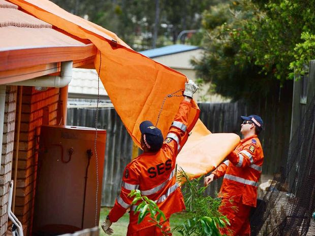 DAMAGE COVER: SES crews cover the damaged roof of a house in Deebing Heights after it was struck by lightning on Saturday.