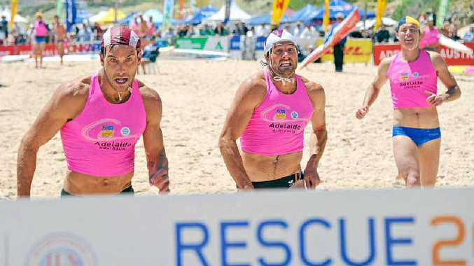 Mooloolaba's Matt Poole crosses the finish line first in the oceanman relay at the World Lifesaving Championships.