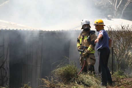 Fire fighters work to extinguish a fire on Brookland Rd, Tinbeerwah. Photo: Darryn Smith / Sunshine Coast Daily