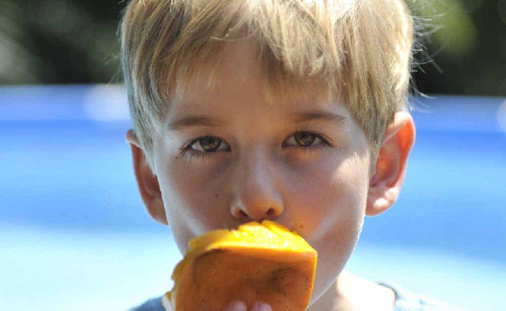 Finn Campbell eating a refreshing mango.