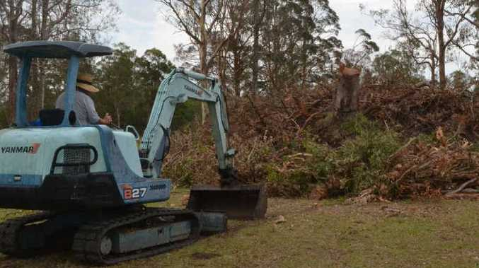 DEBRIS MOUNTAIN: A golf club volunteer moves storm rubbish into one of six huge piles of debris around the golf course.