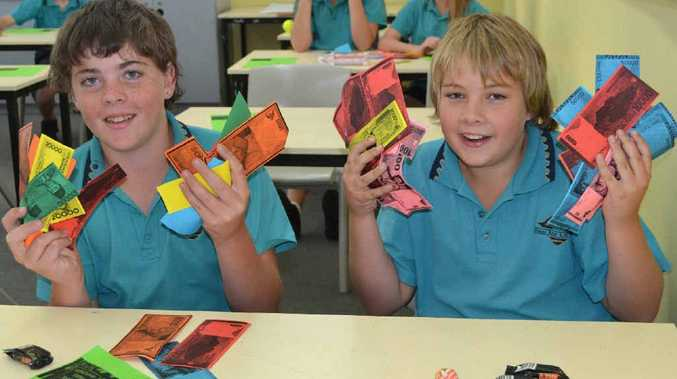 EXPENSIVE AUCTION: Chris Greaves, 13, and Billy Brown, 12, show off the Indonesian play money they used in the Evans River School auction.