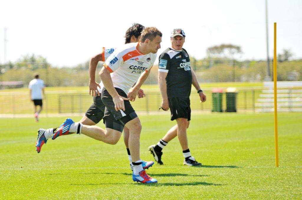 Besart Berisha (closest to camera) sprints under the gaze of coach Rado Vidosic, during a Brisbane Roar team training session at Stockland Stadium.