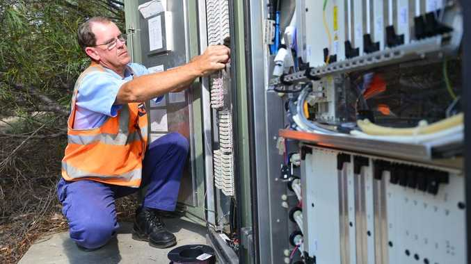 A file picture of a Telstra communication technician installing ADSL2+ infrastructure.