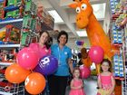 Toys R Us staff Melissa McCurley, Catherine Murrell and Geoffrey the Giraffe met young shoppers Rylie Bryson and her sister Kayla Bryson when the store reopened at the Showgrounds on Saturday.