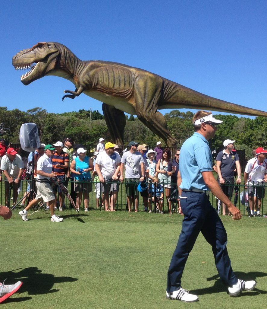 Robert Allenby walks past Clive Palmer's pet dinosaur