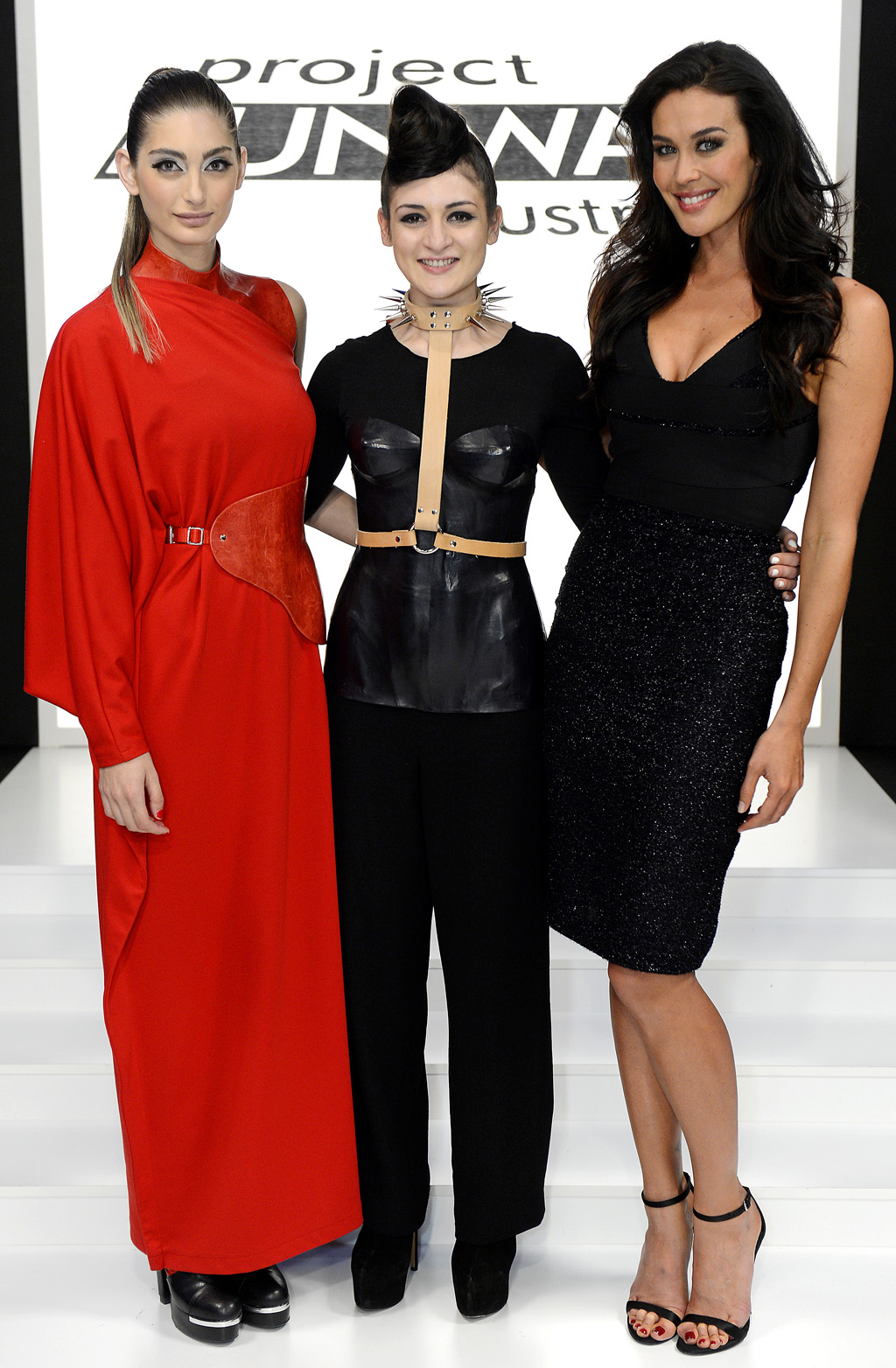 Project Runway winner Christina Exie pictured with host Megan Gale, right, and a model wearing a piece from her winning collection.
