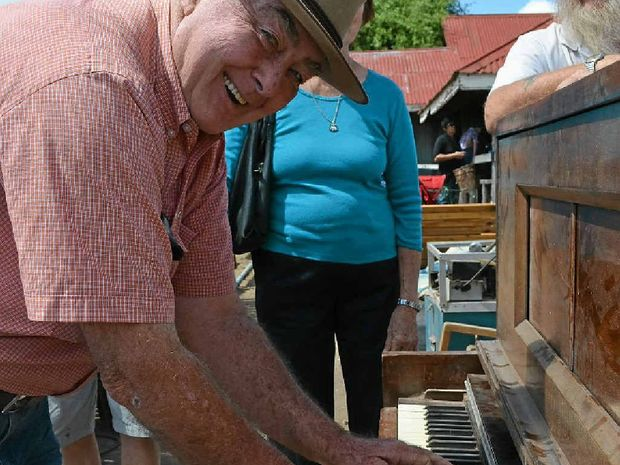 PLAY ANOTHER ONE SAM: Retired local policeman and former dance band player Col King attracted an audience playing a pianola at the pig and calf sale.