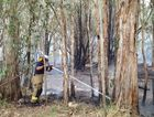 Bushfires at Sunshine Acres and Springvale Downs - A firefighter damps down smoldering embers.