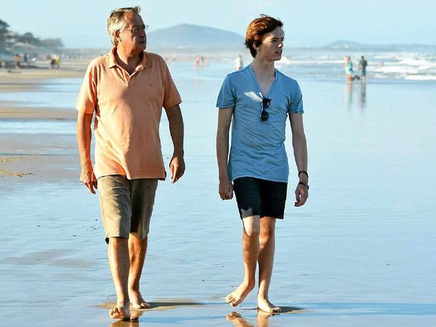 Federal Treasurer Wayne Swan and his son Matt enjoy a walk on the beach while holidaying on the Sunshine Coast.