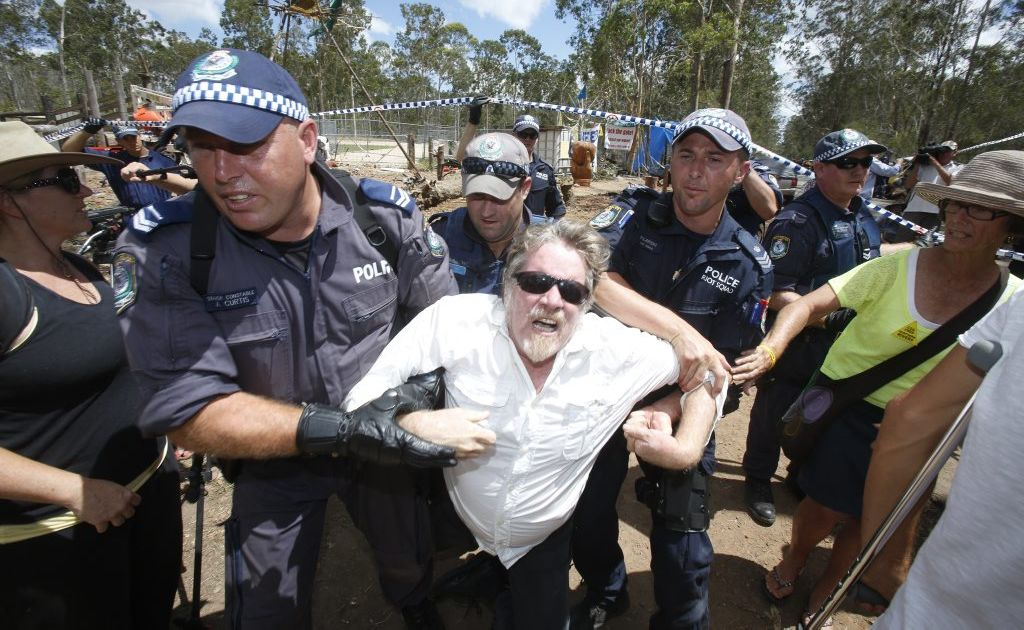 A man is forced out of the line by police as they move people back along the avenue as the road is closed around the Glenugie CSG site. Photo Adam Hourigan / The Daily Examiner