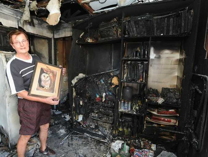 John Braun in the burnt out remains of his home at Fraser Shores Retirement Village holding a painting he did six years ago of an owl that is his wife Mary's favourite.