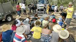 Protesters sit down in front of a truck carrying equipment to the Glenugie CSG site.