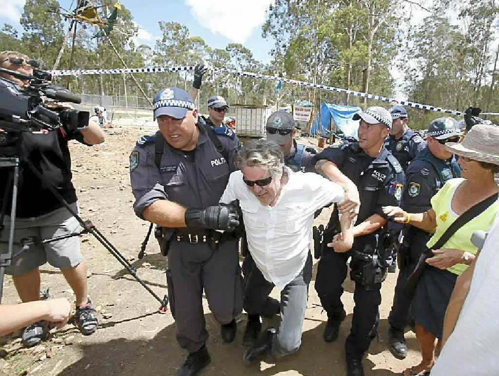 A man is forced out of the line by police as they move people back along The Avenue as the road is closed around the Glenugie CSG site.