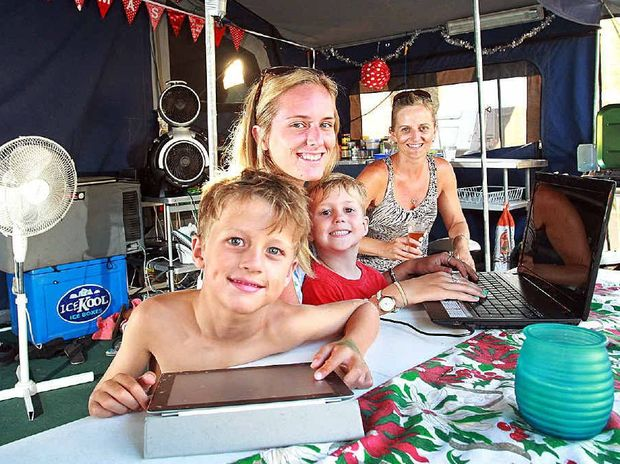 Glam campers (from left) George Gillan, Jacob Kidd, Carlee Foxwell and Mel Foxwell with all their mod cons at Mooloolaba, including laptops, iPads, fridge, toilet, an iron and a pizza cooker.
