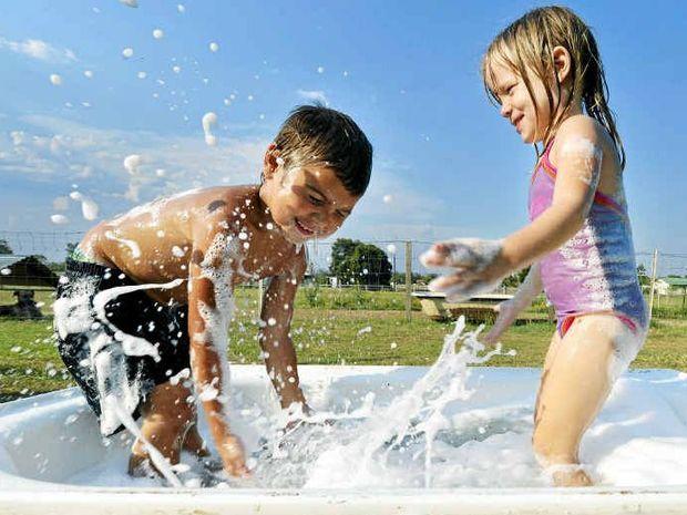 Cousins Latrell Devlin, 5, and Mia Kasper, 3, keep cool in an old bathtub.