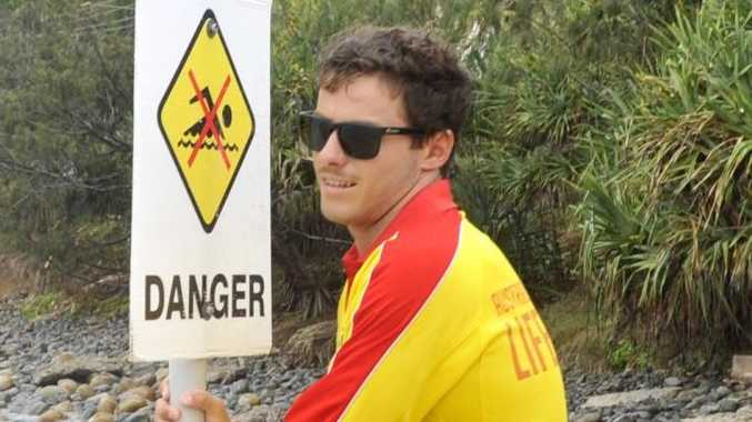 Tom Burns, Byron Bay lifeguard, putting up a sign yesterday warning people not to go swimming after multiple shark sightings. Photo Mireille Merlet-Shaw / The Northern Star