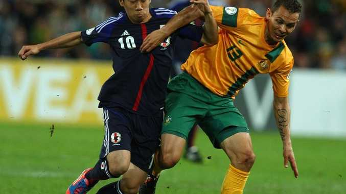 Shinji Kagawa of Japan is challenged by Jade North of Australia during the FIFA World Cup Asian Qualifier match between the Australian Socceroos and Japan at Suncorp Stadium on June 12, 2012 in Brisbane, Australia.