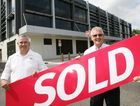 GATEWAY TO CBD: Knight Frank's Neale Crow and Pat O'Driscoll put up the sold sign at the Churchs' site on the corner of Fitzroy and East streets in Rockhampton.