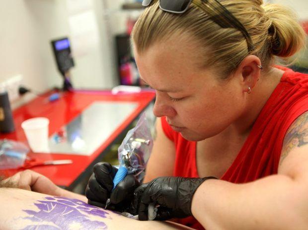 RedBack Ink tatooist Kelly Webb at work on a customers tattoo. Photo Allan Reinikka / The Morning Bulletin