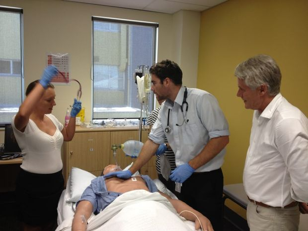 Interns Nicky Poole and Angus McNally in simulation training while MP Geoff Provest looks on. Photo: Luke Mortimer