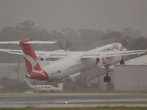 Facebook liker Jamie Chinery sent in this photo of a Qantaslink flight to Brisbane taking off from Gladstone airport in the rain this morning. Rain can be seen spiralling off the blades.
