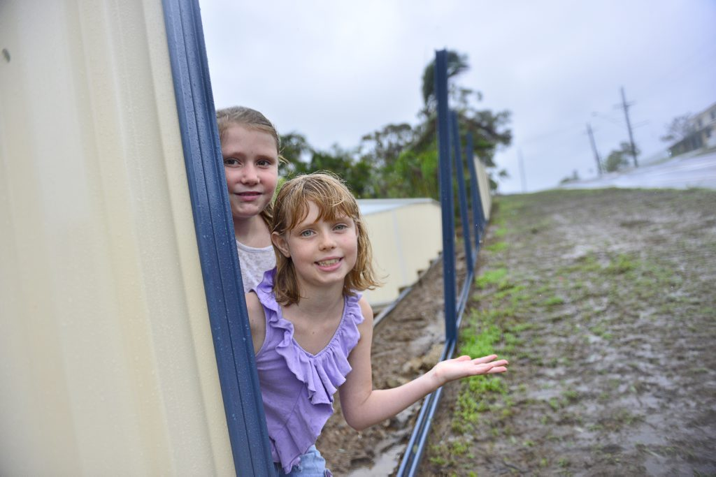 Shaylah, 10, and sister Holly Combridge, 9, had their back fence torn apart due to the severe weather in Gladstone.