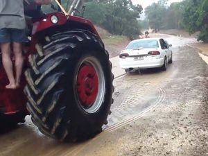 Tractor pulls car from floodwaters