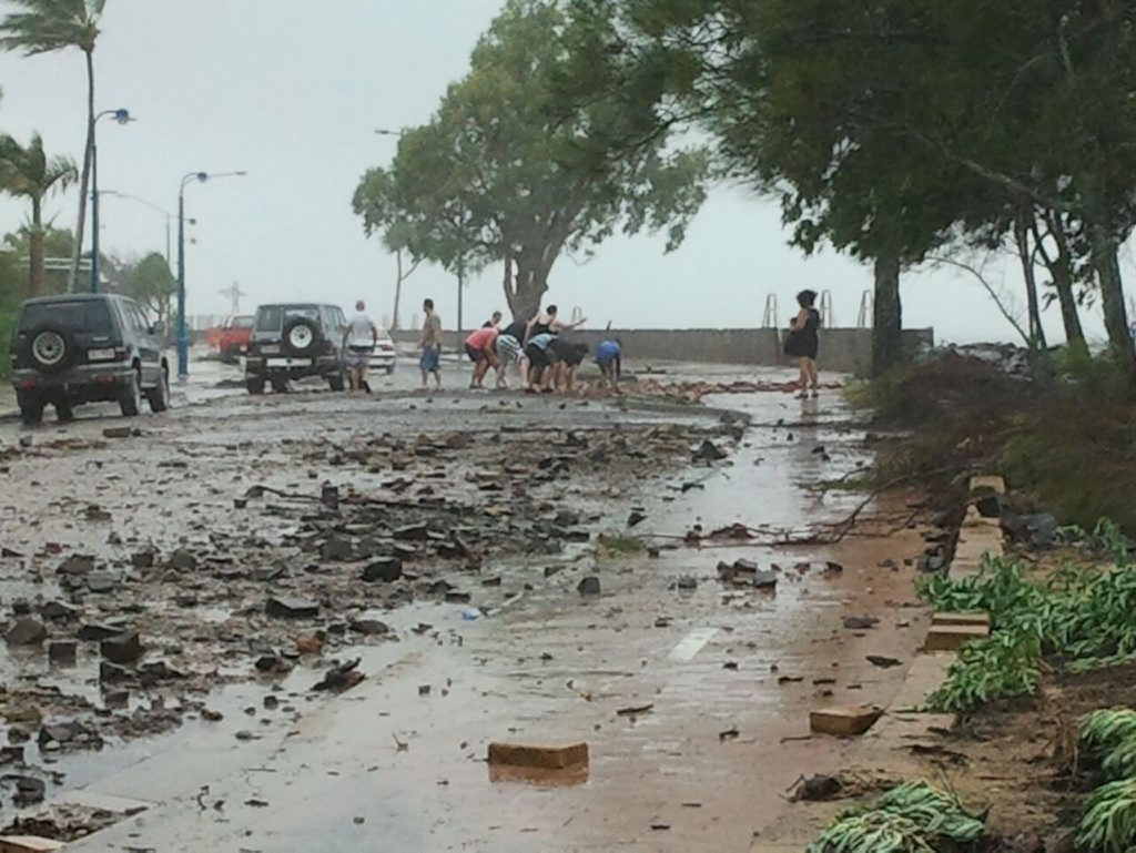 Passersby stop to pick up rocks and pavers strewn about after high winds and abnormally high tides pushed waves over the rock wall at Urangan on Sunday morning. Photo: Valerie Horton