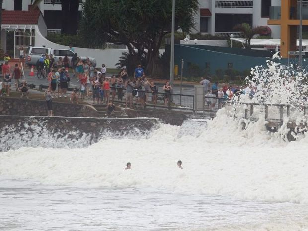 A couple of young men swim in the foam at Alexandra Headland.