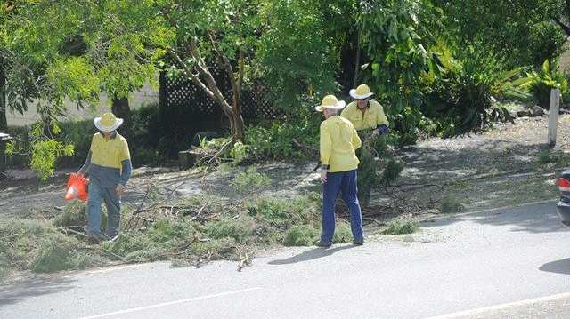 Lismore City Council workers assist with the cleanup along the Bruxner Highway near Goonellabah.