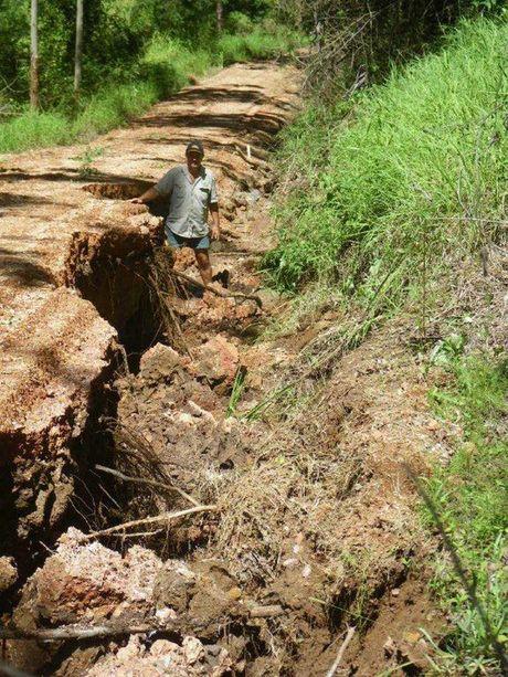 Sunnyspot Packhouse owner Daryl Boardman surveys damage to Case Rd at Ravensbourne.